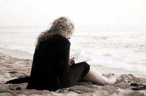 Frau sitzt an ruhigem Stran und schreibt.